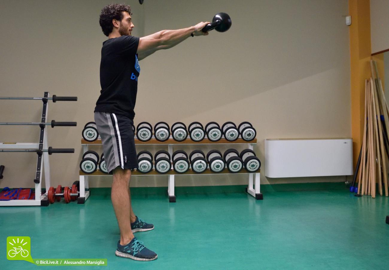 Nella posizione finale l'attrezzo dovrà arrivare all'altezza della testa; schiena sempre in tenuta e pronta a opporsi al movimento di ritorno.