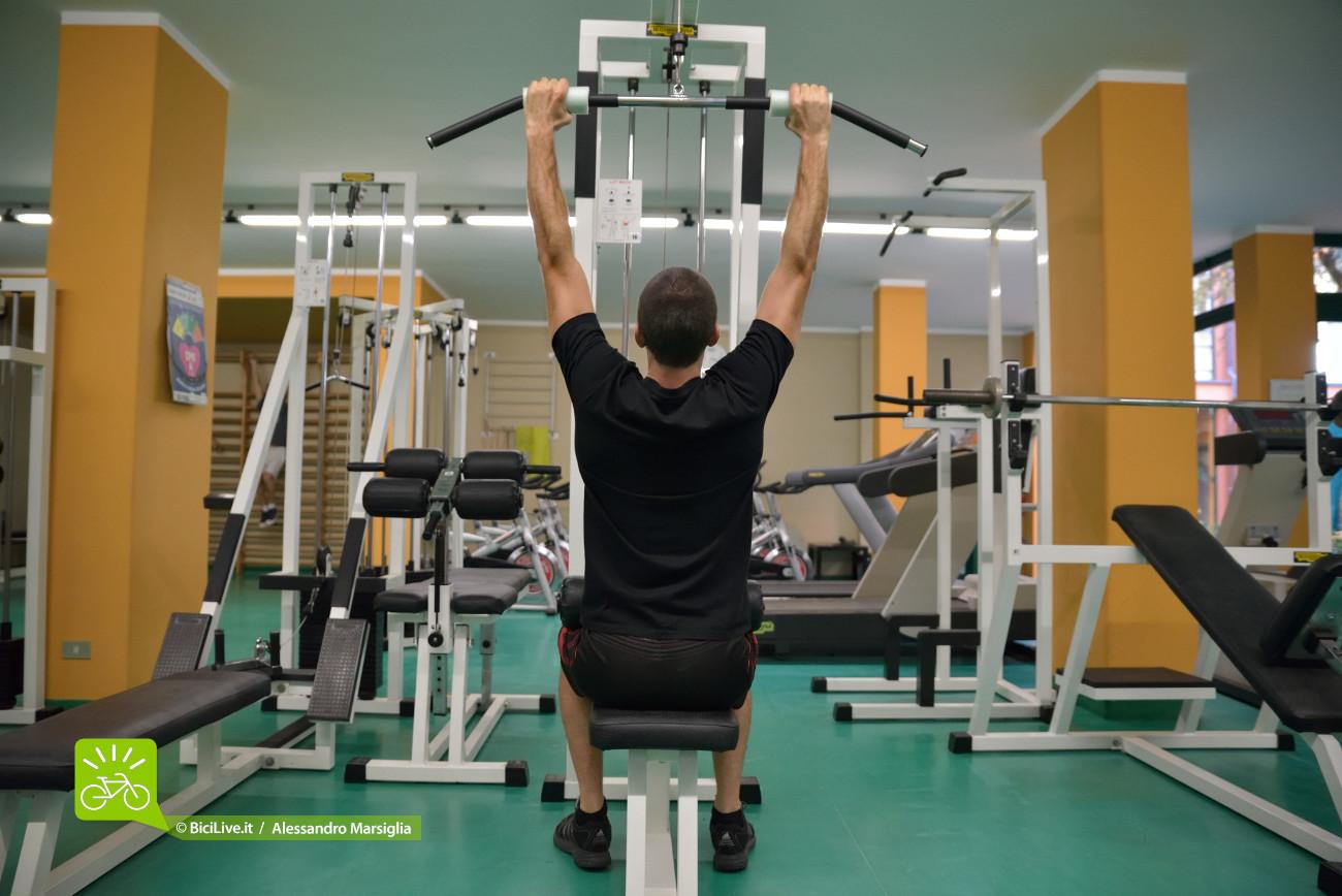 Posizione iniziale con braccia distese ma con spalle fissate in basso. La schiena mantiene un leggero arco posteriore.