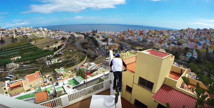 foto di Danny macaskill durante un salto sul tetto delle case a las palmas su un muretto