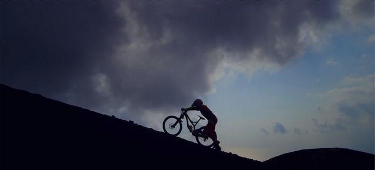 Stevie Smith trascina la sua mountain bike full suspended lungo le spode del vulcano Oyama