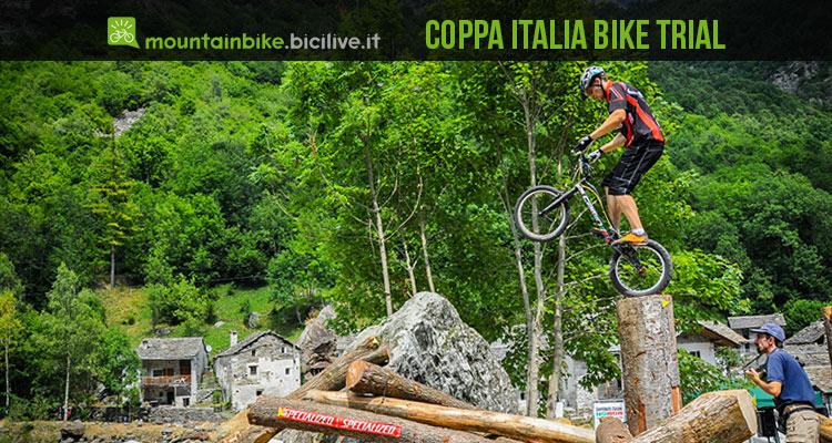 foto di un atleta di bike trial impegnato in un passaggio su un tronco