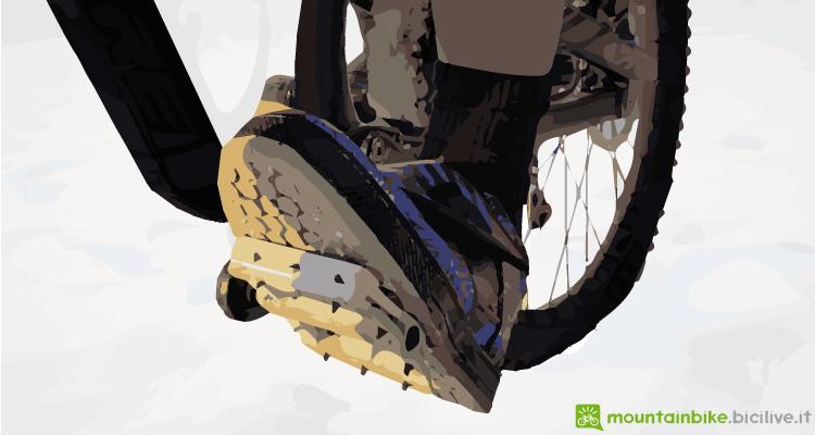 foto di un biker con i pedali flat, in discesa, su una mtb