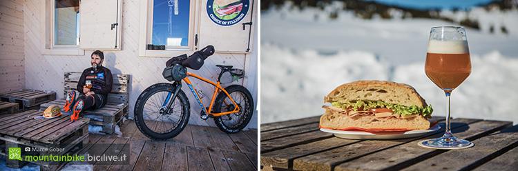 foto di un biker con fat bike e un panino con una birra