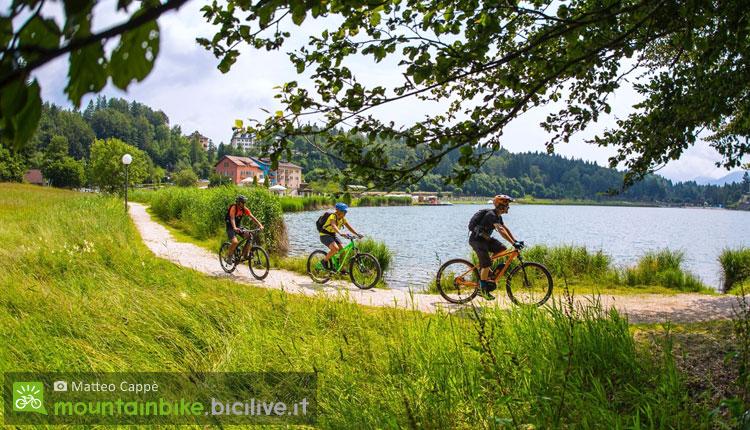 ciclisti pedalano sul lago di lavarone
