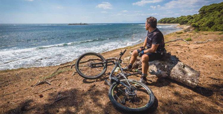Ciclista mtb si riposa in riva al mare dopo una pedalata