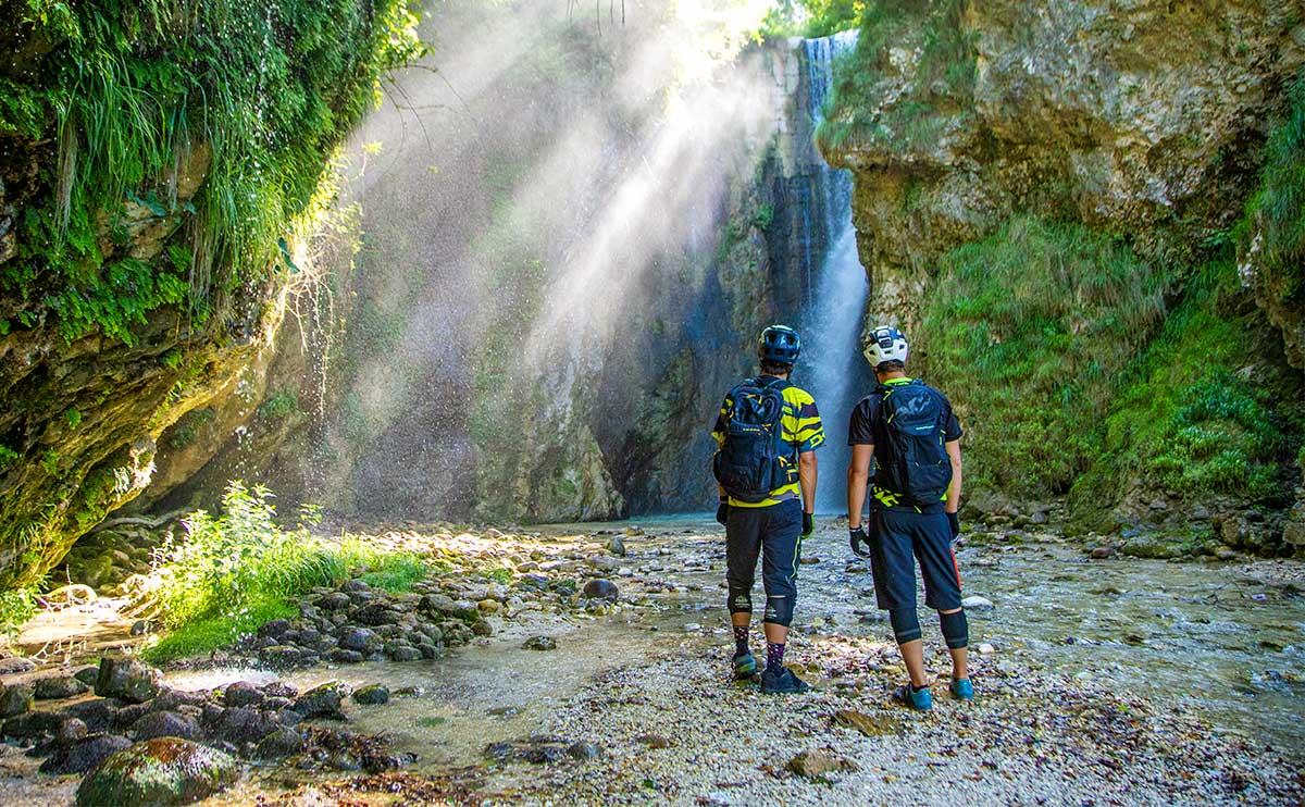 ciclisti che osservono una cascata all'Alpe Cimbra