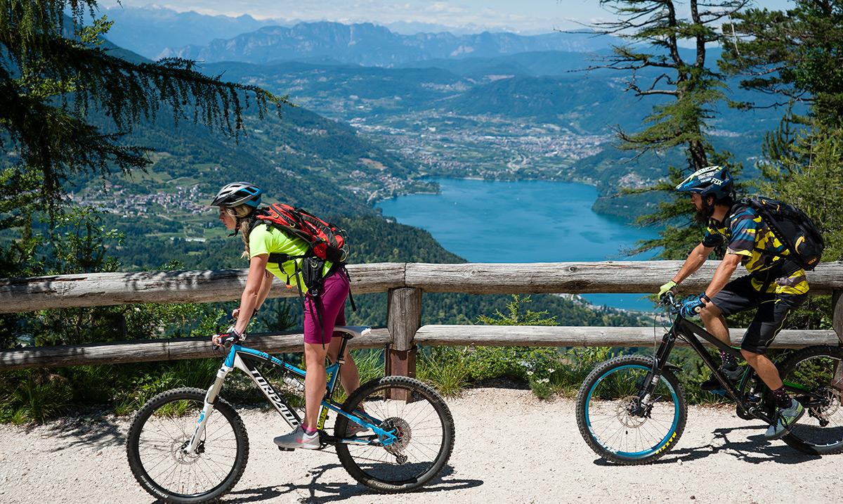 ciclisti su una ciclabile con vista su un lago del Alpe Cimbra