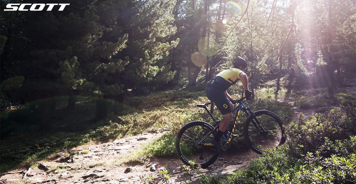 Ciclista in sella alla Scott Spark RC 900 affronta un sentiero tra i boschi