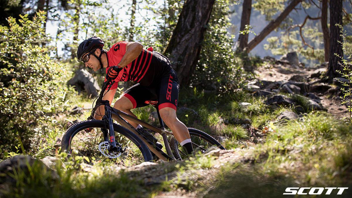 Un rider pedala nel bosco in sella a una mtb 2020 Scott