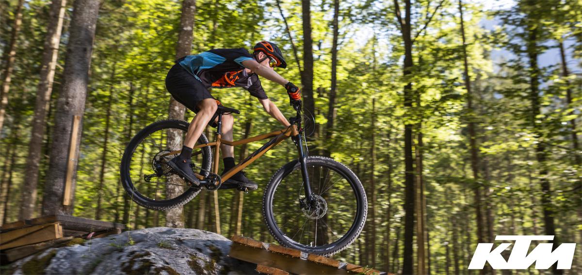 Rider salta nei boschi in sella a una mtb front KTM Ultra EVO 2020