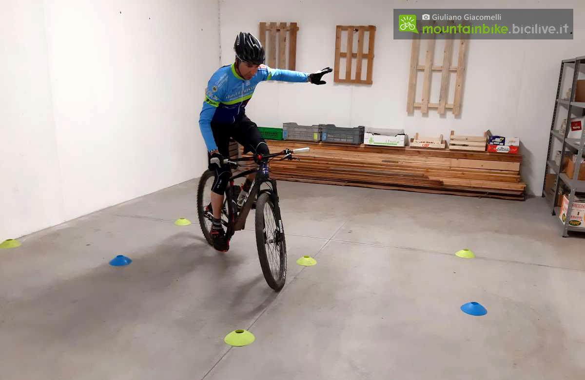 Ciclista esegue l'esercizo dell'otto con una mano sola e in piedi sui pedali della mtb