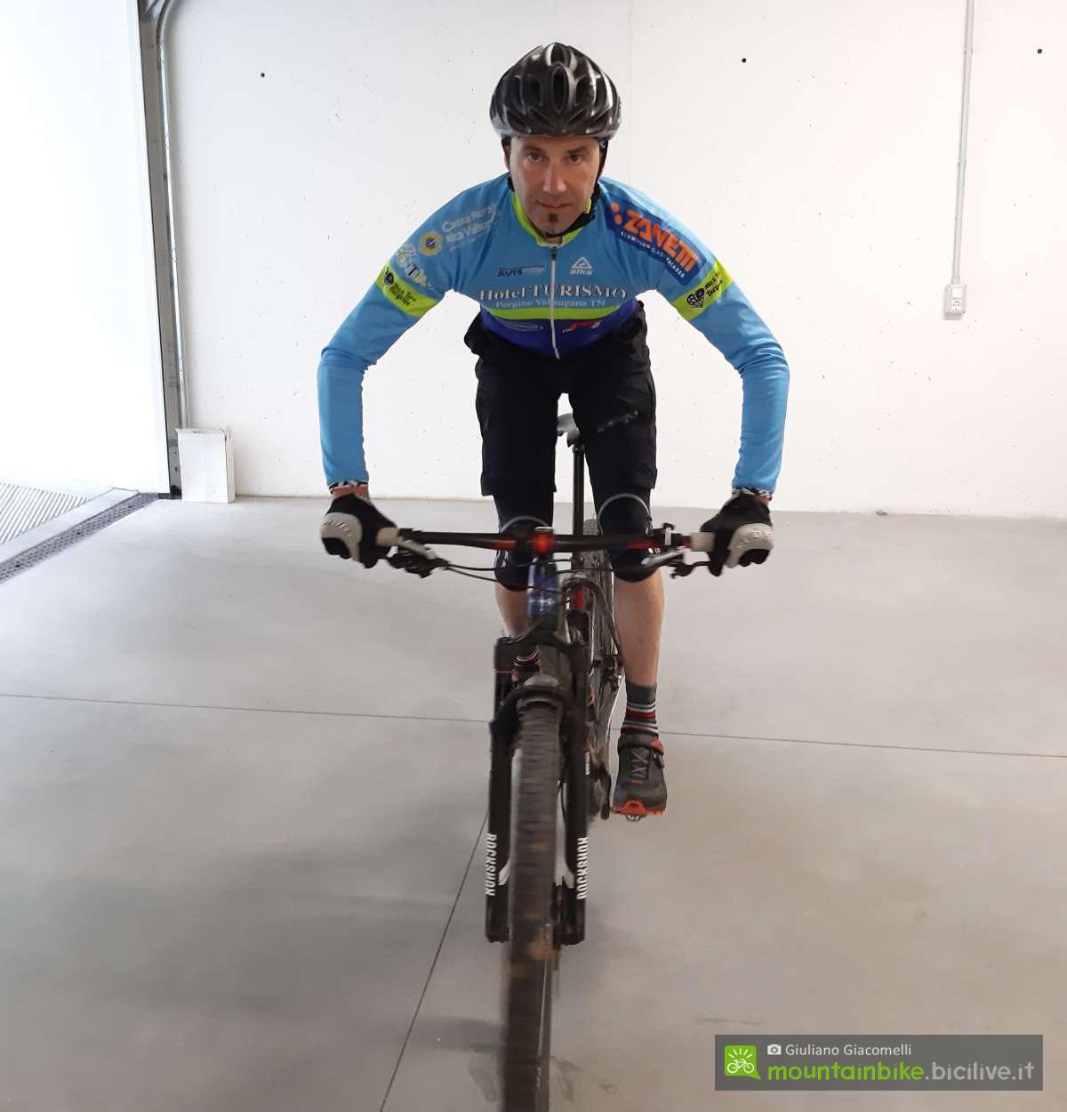 Rider mtb mostrala posizione base vista di fronte con i gomiti all'esterno
