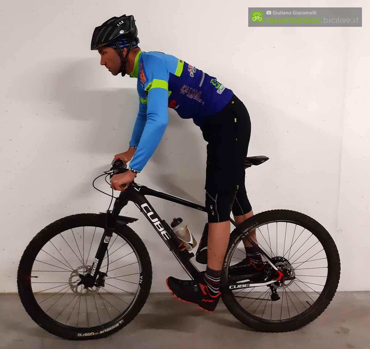 Ciclista in posizione base per iniziare gli esercizi in mountain bike