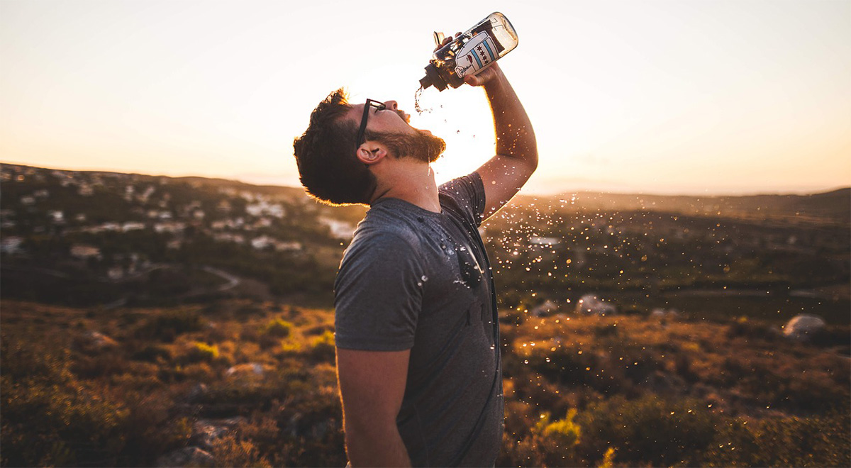Uomo che beve avidamente da una borraccia
