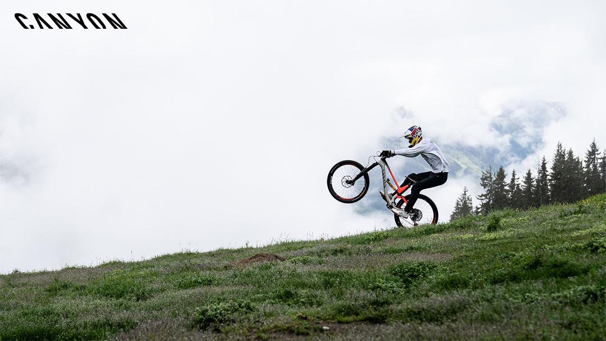 Un rider impenna sopra alla sua nuova mtb Canyon Sender AL