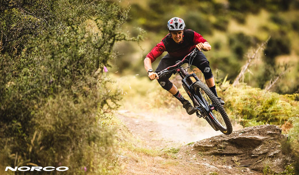 Un rider MTB si diverte in discesa in sella a una Norco Sight C2 Shimano 2021