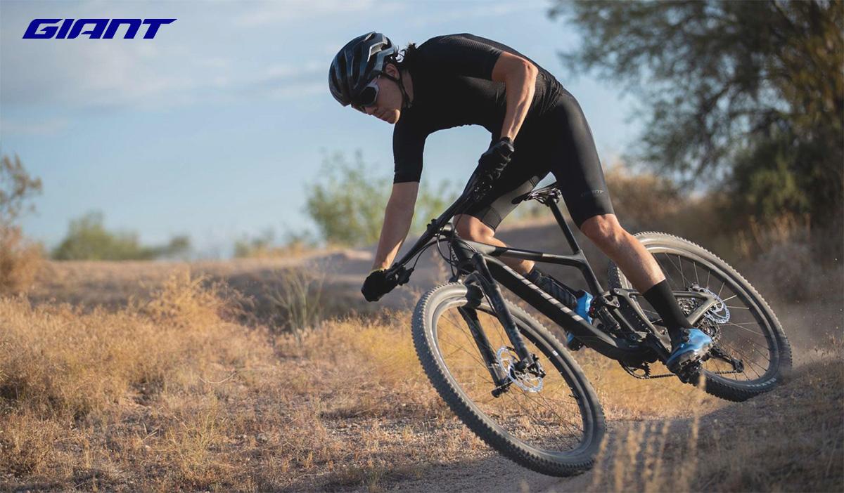 Un rider pedala sullo sterrato in sella ad una nuova mountainbike Giant 2021