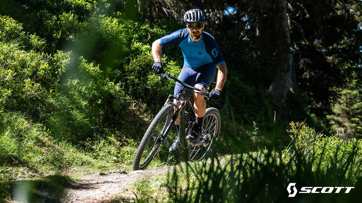 Un uomo pedala in sella ad una nuova mountainbike Scott 2021