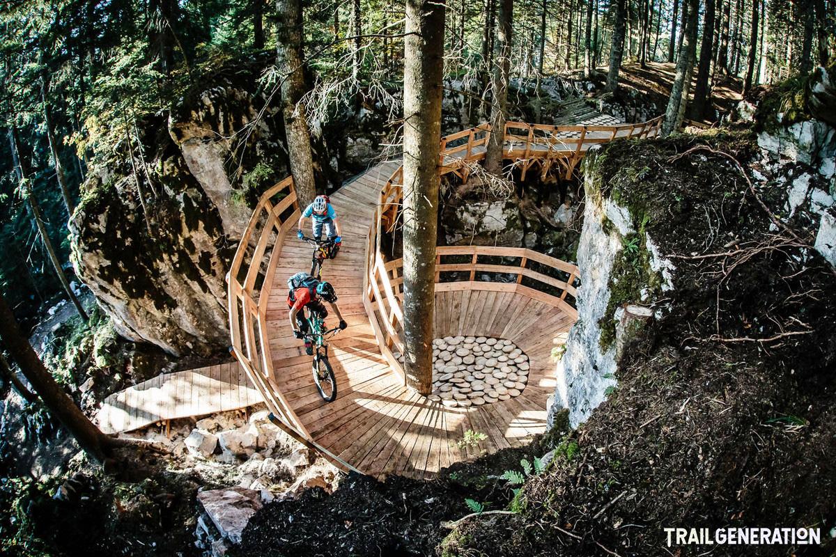 Due rider MTB scendono da una struttura in legno costruita da Trail Generation