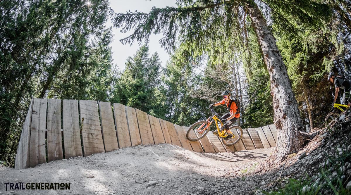 Un rider MTB pedala su una struttura in legno di una pista creata da Trail Generation