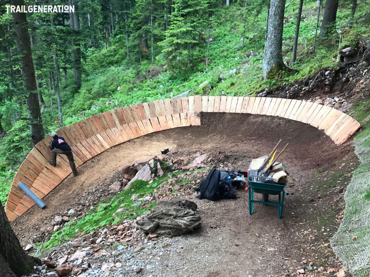 Un trail builder di Trail Generation lavora a una struttura in legno su una pista MTB