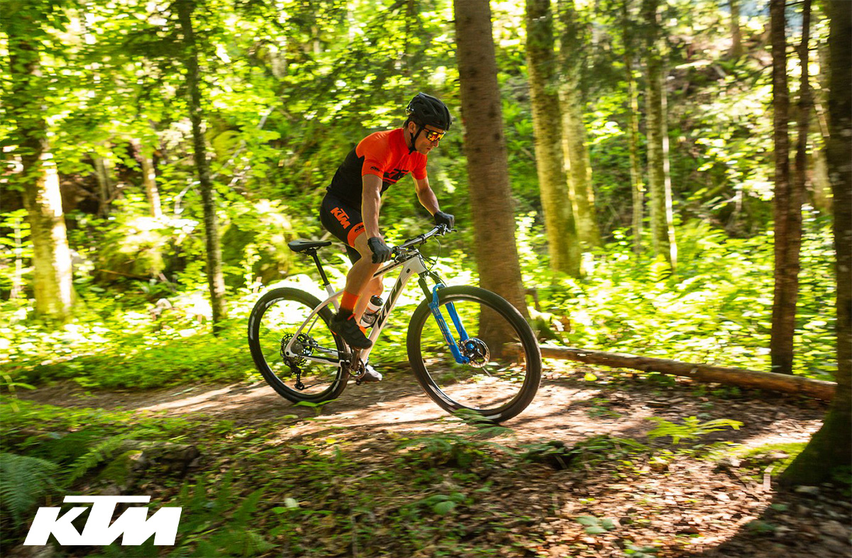 Un rider pedala nel bosco in sella ad una mountainbike full Ktm