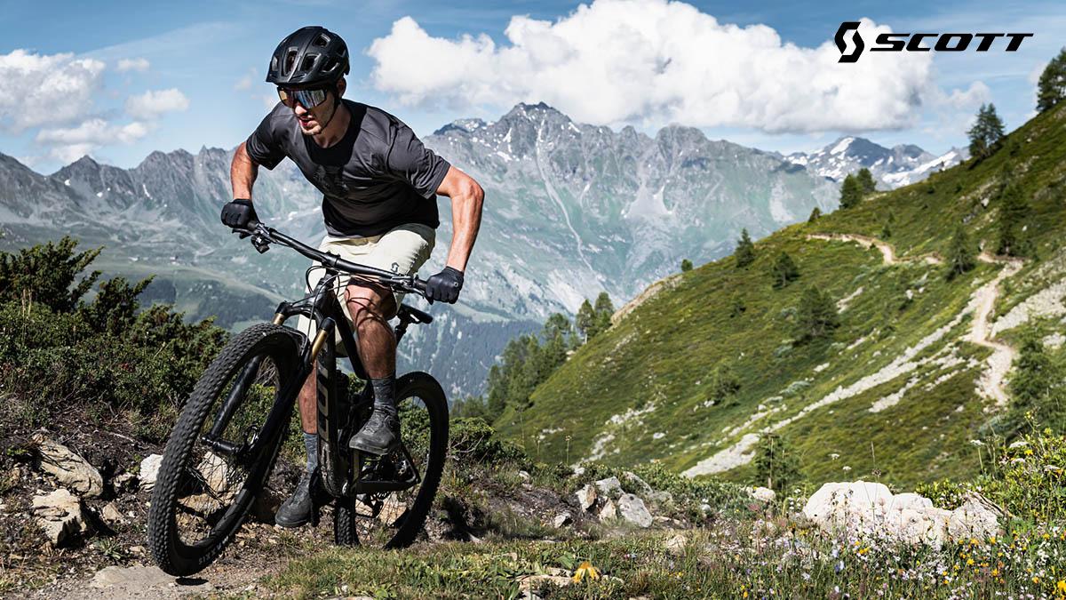 Un rider pedala nel bosco in sella ad una mtb Scott