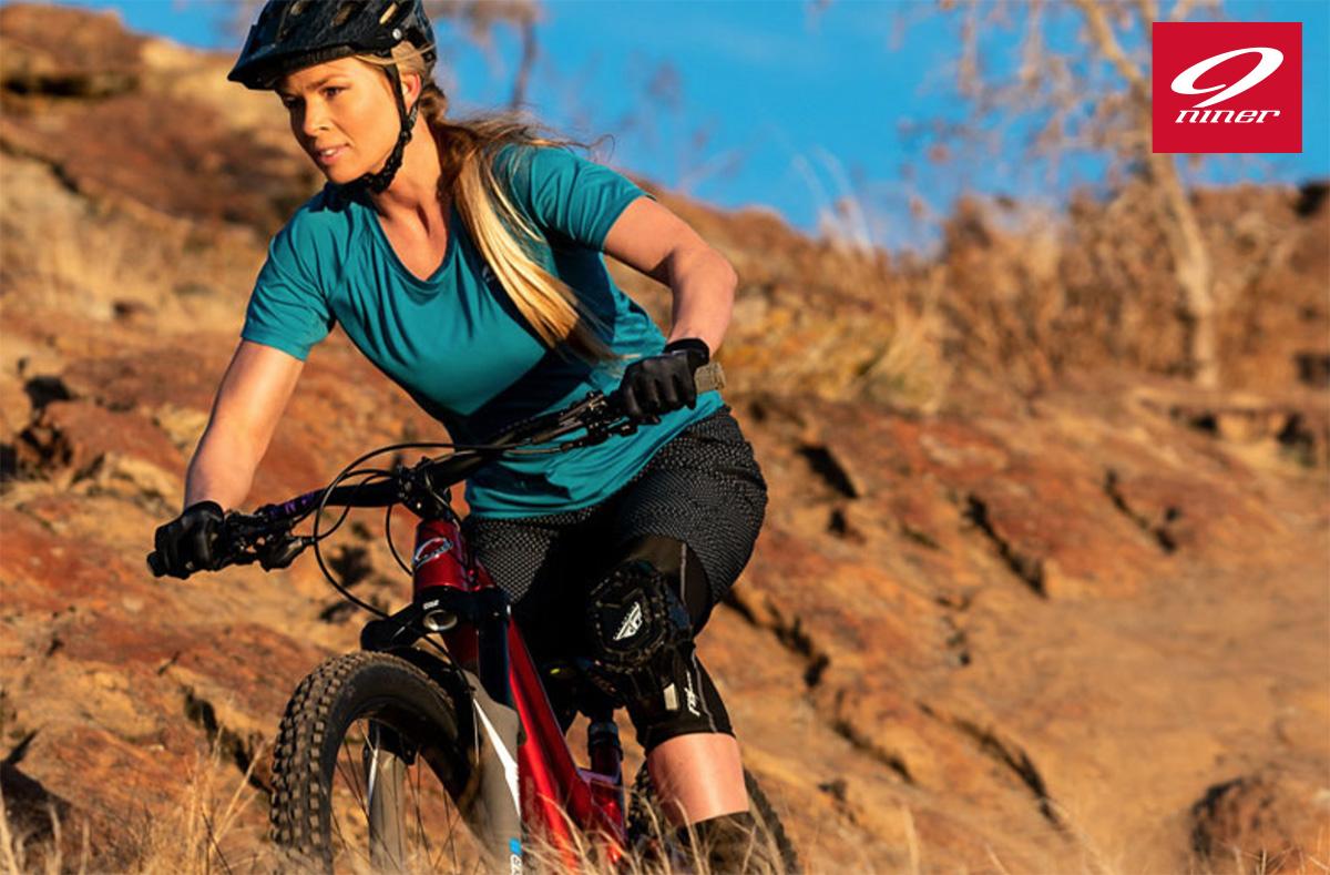 Una ragazza pedala sulla nuova mtb full Niner WFO 9 RDO 2021