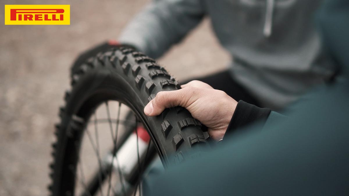Una mano stringe tra le mani il copertone Pirelli Scorpion per MTB