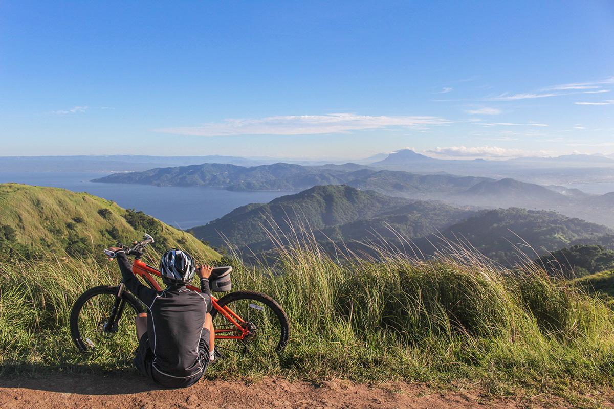 Un uomo contempla l'orizzonte di un panorama montano con la sua mountainbike