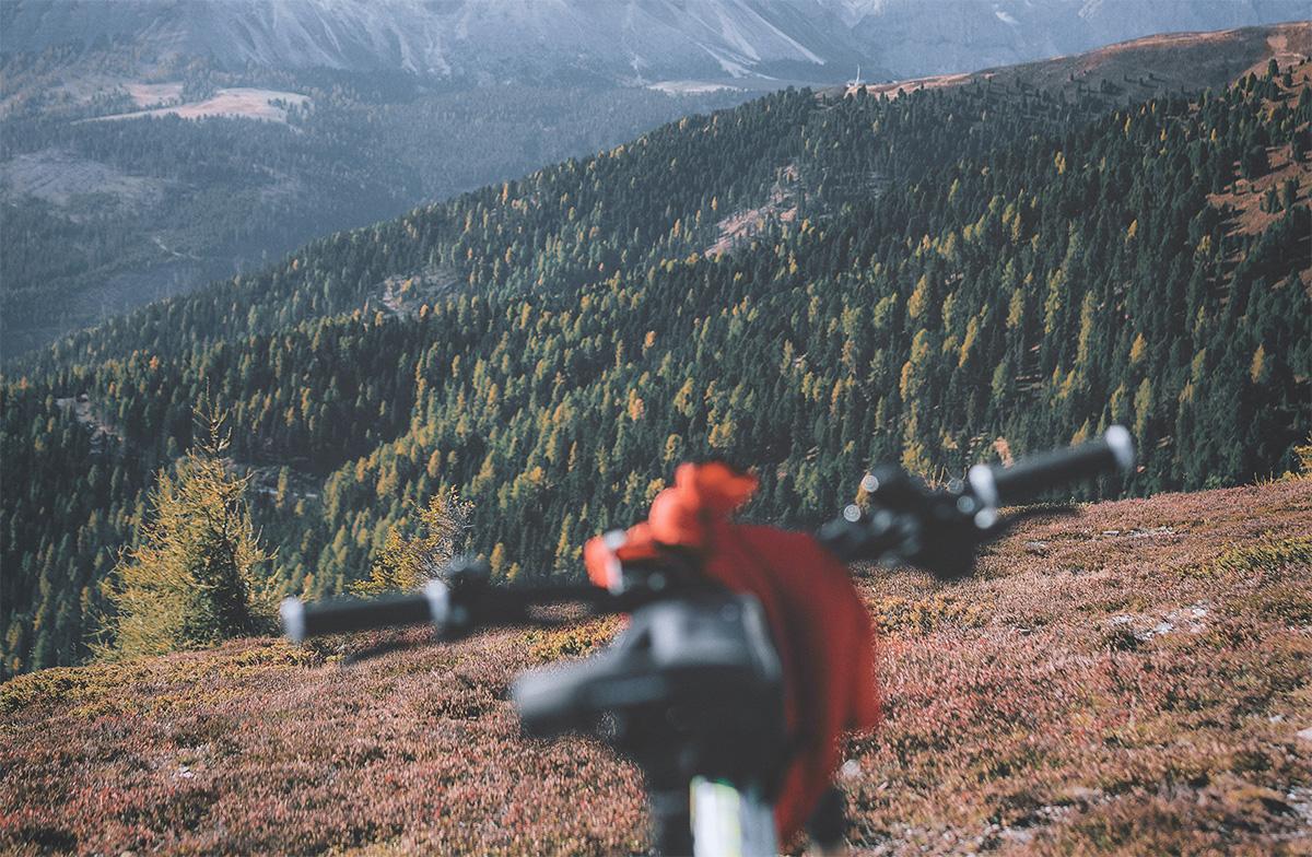 Una mountainbike posizionata su una collina che guarda verso il panorama montano