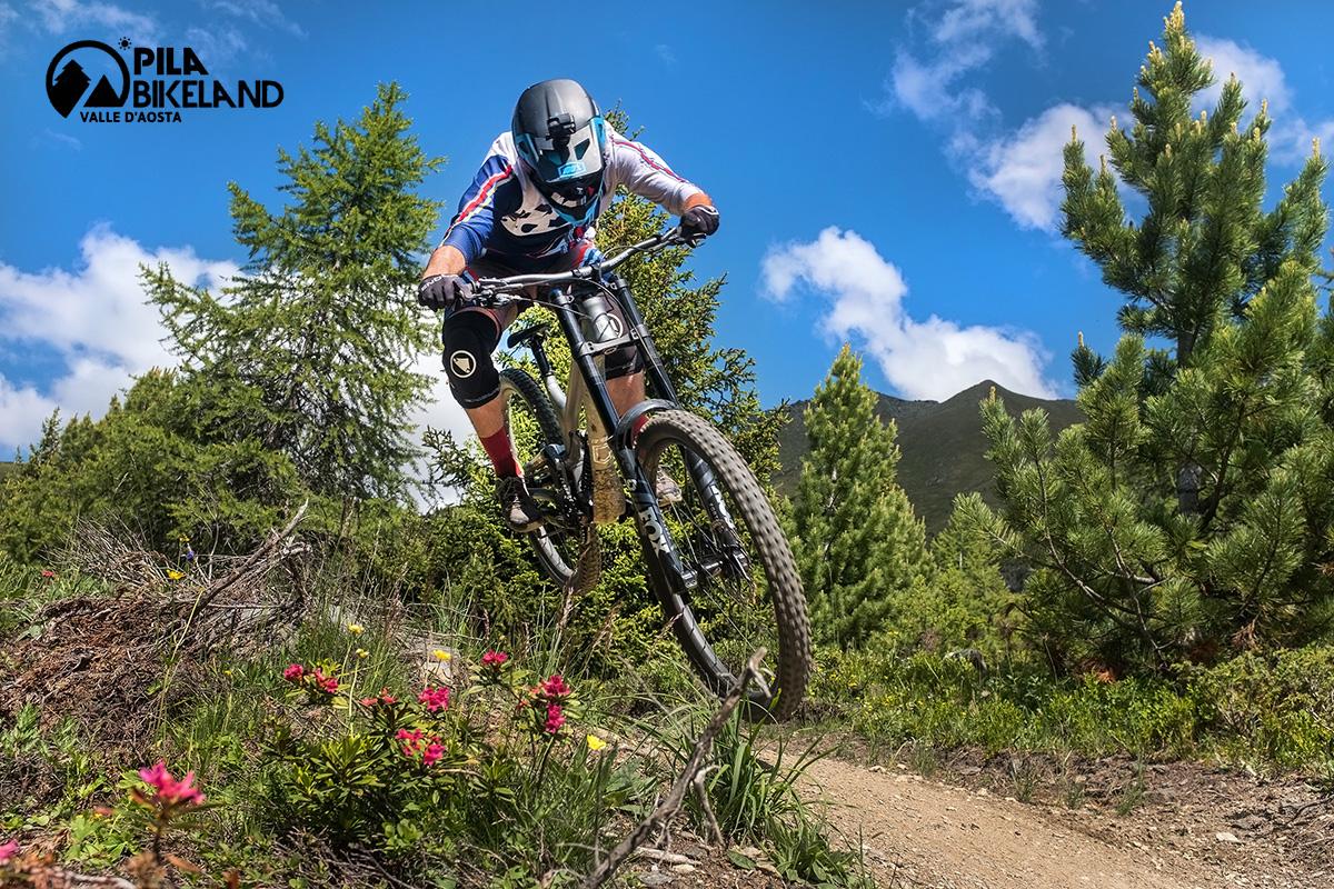 Un rider compie un salto su uno sterrato del Pila Bikeland con la propria mountainbike