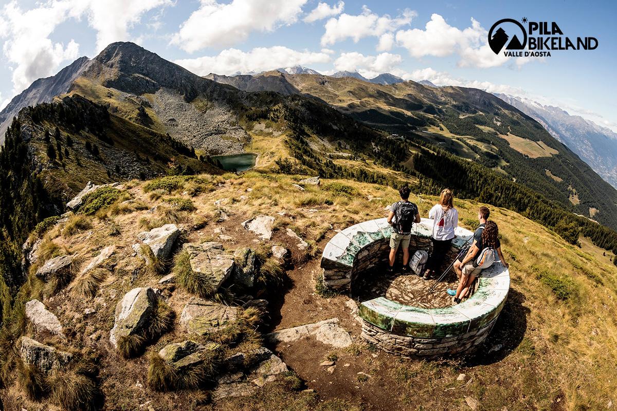 Dei ragazzi fanno trekking in cima ad una collina ammirando il panorama del Pila Bikeland