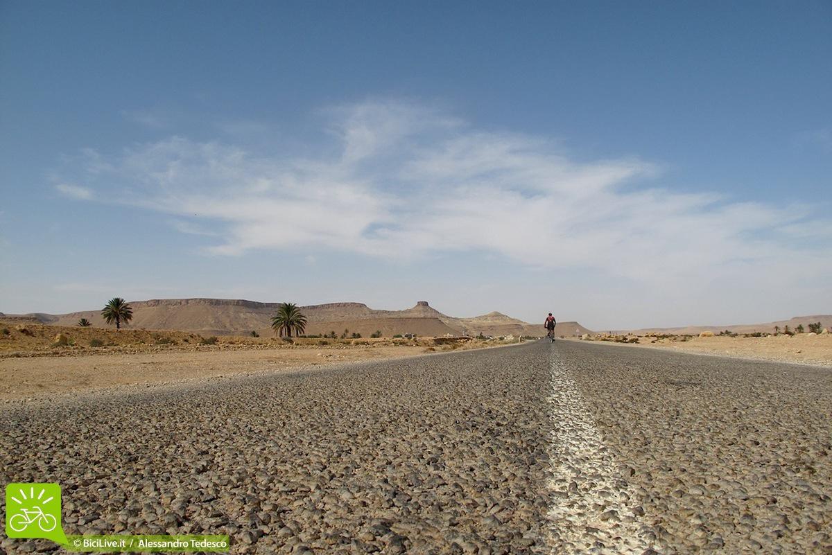 Ciclista in mezzo a strada nel deserto